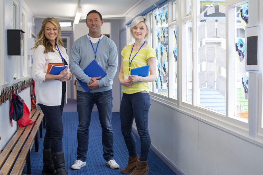 Three teachers standing in the corridor of a school building. They are holding school work and smiling at the camera.